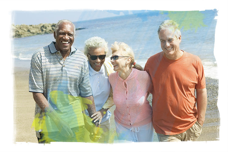 African American and caucasian mature couples walking on beach, laughing