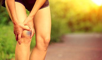woman runner holding bruised knee