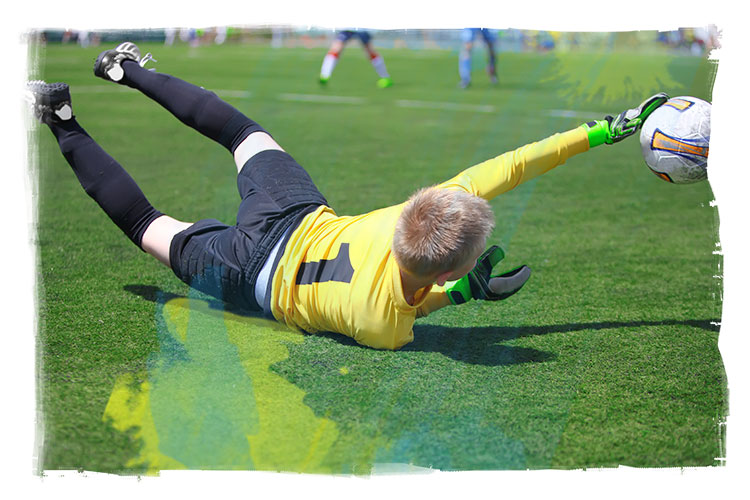 Kids soccer goalkeeper catching a low ball on the ground