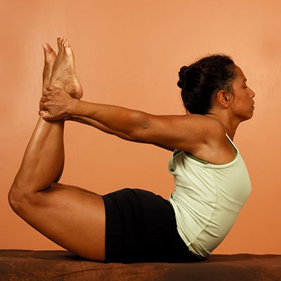 Take aim at rounded shoulders with Dhanurasana.