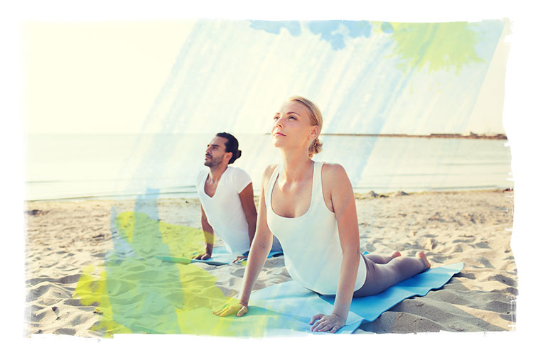 man and woman in upward dog position on beach