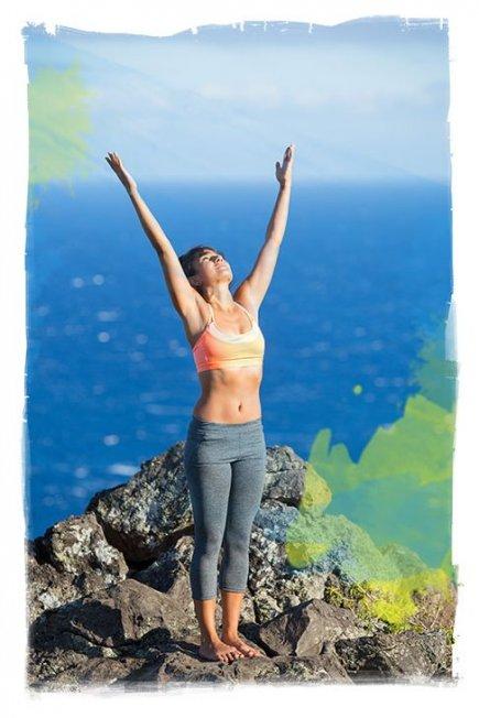 woman doing sun salutations on a rocky shoreline