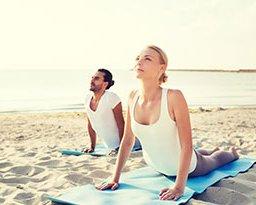 couple doing yoga on beach