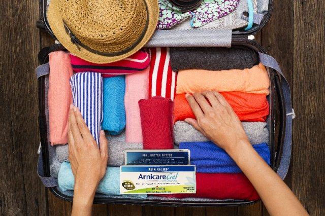 woman packing for trip with arnicare