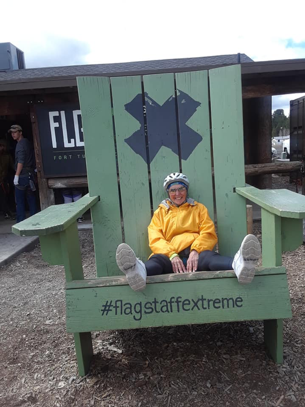 Carol sitting in a large green chair with an X and #flagstaffextreme